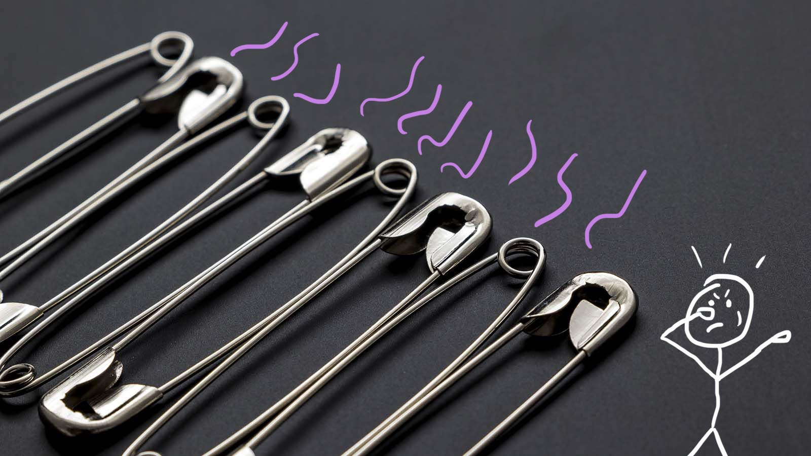Silver safety pin sewing isolated black background